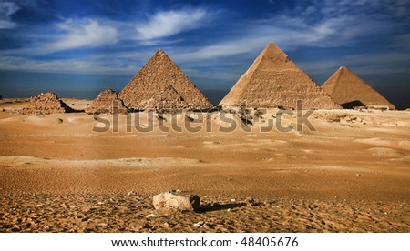 Near to the city of Cairo, in Sinai desert, against the pure blue sky and clouds, pyramids, an ancient miracle of the world have settled down - stock photo