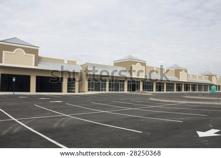 nearly complete empty commercial strip mall with tin roof accents