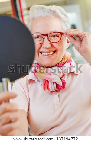 Nearsighted senior woman with new glasses looking into mirror at optician - stock photo