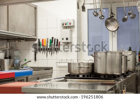 Neat interior of a commercial kitchen with wall mounted utensils and a range of different stainless steel pots arranged on a central gas hob