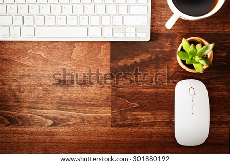Neat workstation on a wooden desk viewed from overhead with a wireless computer mouse and keyboard, cup of coffee and houseplant - stock photo
