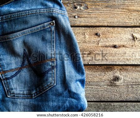 Neatly folded jeans on wooden background. Clothing, fashion, style, lifestyle - stock photo