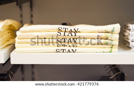 Neatly folded shirts with word STAY - stock photo