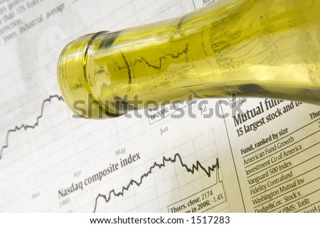Neck of wine bottle above financial page of newspaper - stock photo