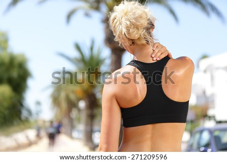 Neck pain during training. Athlete running Caucasian blond woman runner with sport injury in sports bra rubbing and touching upper back muscles outside after exercise workout in summer. - stock photo
