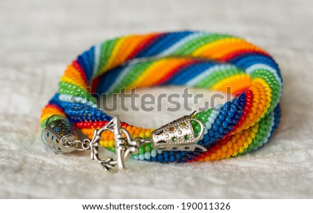 Necklace from beads of a rainbow colors on a textile background