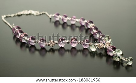 necklace made of transparent amethyst and prasiolite on a black background - stock photo