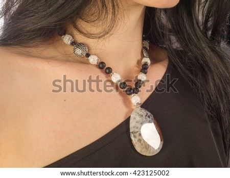 necklace on the girl's neck, a necklace of colored semi-precious stones - stock photo