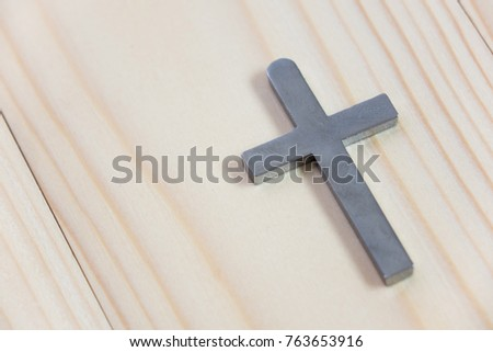 Necklace with silver cross on wooden table