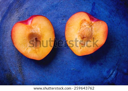 Nectarine halves in the shape of heart over blue ceramic background. Top view. - stock photo