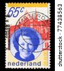 NEDERLANDS - CIRCA 1980: A stamp printed in Nederlands shows woman and building 65c 30-IV-80, circa 1980 - stock photo
