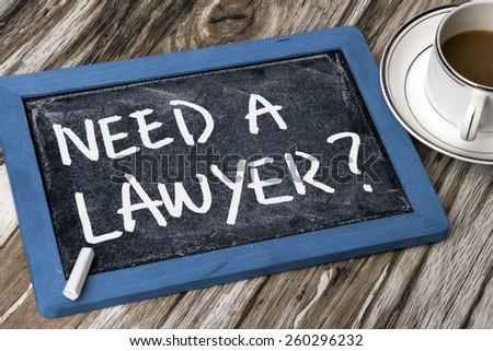 need a lawyer handwritten on blackboard - stock photo