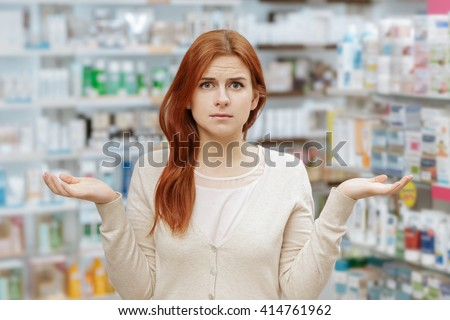 Need help. Portrait of a young frustrated woman looking to the camera at the local drugstore. - stock photo