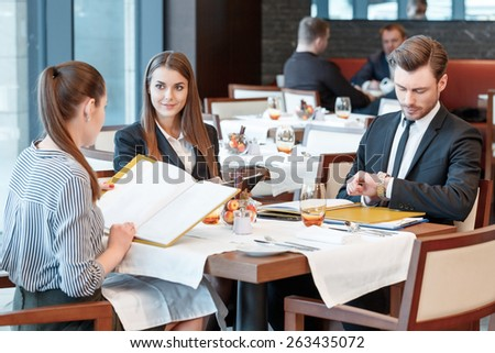 Need to control timing of the meeting. Businesswomen at the lunch table look at other and their male colleague looks at the watch to check the time - stock photo
