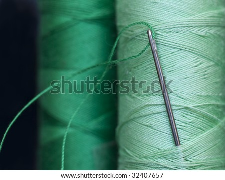 needle and green bobbins - stock photo