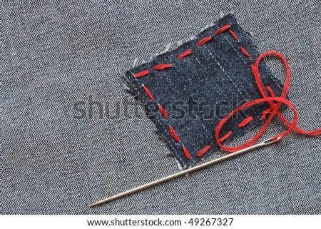 Needle and patch with red thread attached on jeans textured - stock photo
