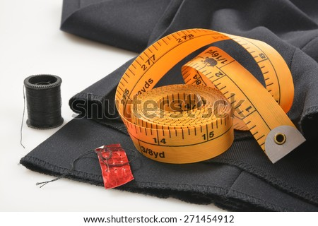 Needle and tread with a measuring tape on pants that need a hem put in - stock photo