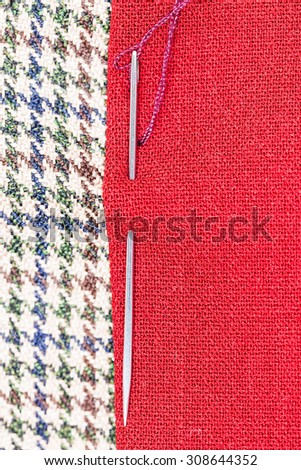 needle sews two pieces of fabric close up - stock photo