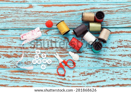 needle thread sewing tailor thimble buttons scissors repair background  blue wood  teak still life vintage color - stock photo
