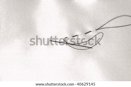 needle with black yarn in white sateen - stock photo