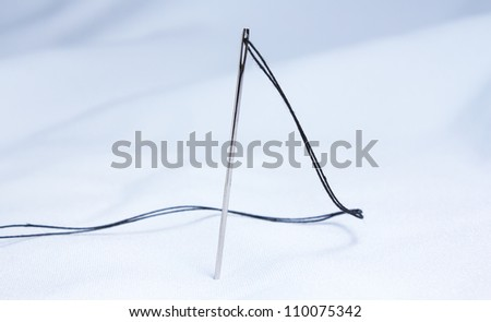needle with thread on fabric - stock photo