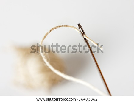 Needle with thread with ball on background - stock photo