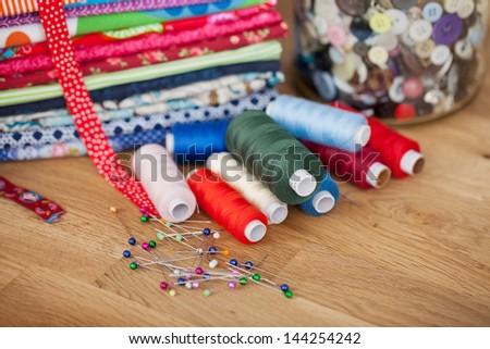 Needlework and handicraft concept with bright colorful fabric, thread, pins and buttons displayed on a wooden counter - stock photo