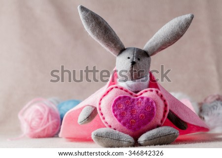 Needlework hobby concept. Handmade bunny with soft heart on soft background