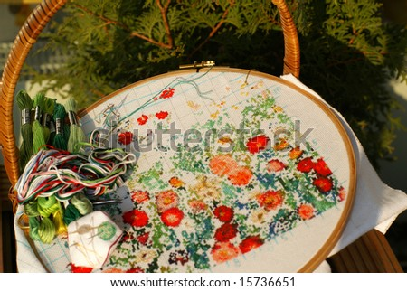 needlework of generic flowers on textile (cross stitch) - stock photo