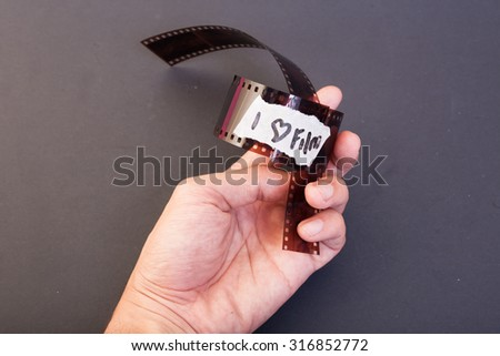 """Negative film on the hand and have a signage """"i love film"""". This photo apply side lighting and use black background - stock photo"""