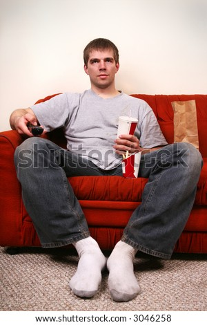 negative side of american lifestyle - a bored young man on a couch with a tv remote and junk food - stock photo