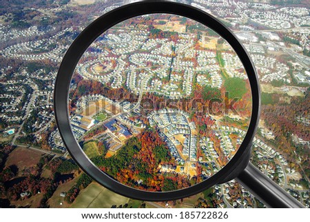 Neighborhood from the air with magnifying glass - real estate concept - stock photo