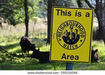 Neighborhood watch sign in cow paddock, Scotland - stock photo