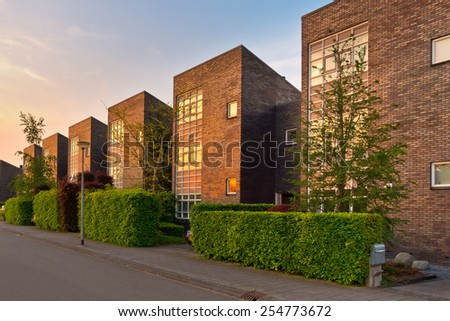 Neighborhood with modern houses in a suburban street in afternoon sun - stock photo