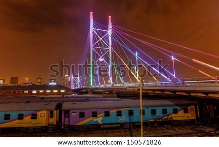 Nelson Mandela Bridge at night. The 284 meter long Nelson Mandela Bridge connecting Newtown, which was opened by Nelson Mandela himself. Seen over the 40 railway lines it helps traverse. - stock photo