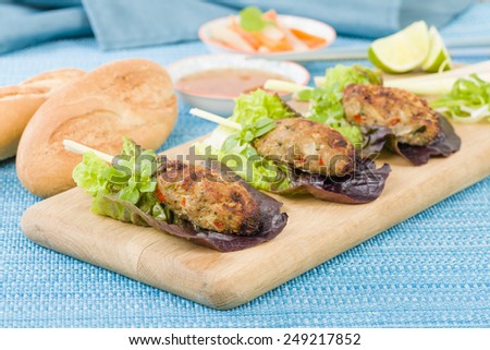 Nem Nuong Xa - Vietnamese minced pork sausages on lemongrass skewers served with do chua, nouc cham and chili sauce. - stock photo
