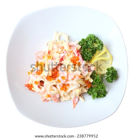 Nemo salad with squid, pepper, lollo Rosso salad, Japanese omelet and mayonnaise on white dish isolated on a white background. There is red caviar on it. Top view. - stock photo