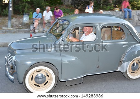 NENDAZ, SWITZERLAND - JULY 27: Proud owner of a vintage Renault in a parade at the International Alpine Horn Festival:  July  27, 2013 in Nendaz, Switzerland - stock photo