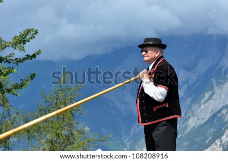 NENDAZ, SWITZERLAND - JULY 21: Toni Kunz with mountain backdrop at the 11th International Festival of Alpine horns on July 21, 2012 in Nendaz Switzerland