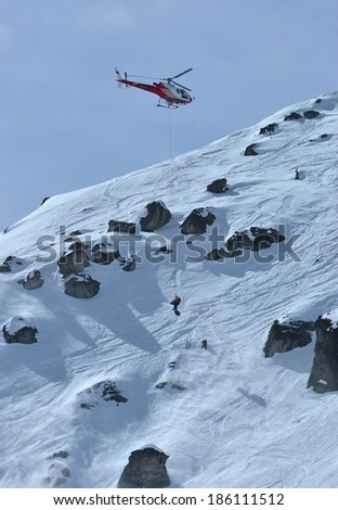 NENDAZ, SWITZERLAND - MARCH 15: A badly injured competitor is rescued from the accident zone by helicopter at the Nendaz Freeride Finals: March 15, 2014 in Nendaz, Switzerland - stock photo