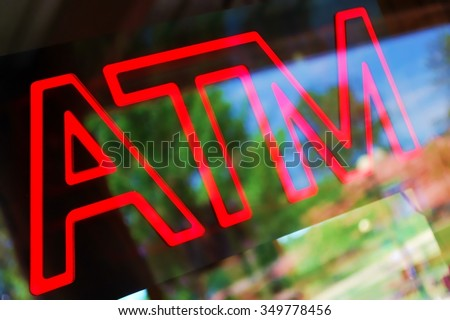 Neon ATM sign against a heavy reflection - stock photo
