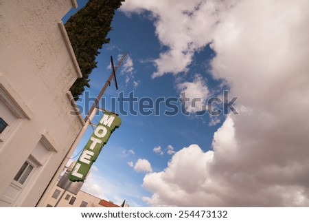 Neon Motel Sign Clear Blue Sky White Billowing Clouds - stock photo