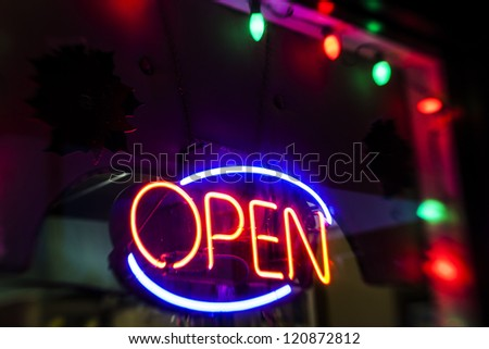 Neon Open sign with Christmas lights and decorations shot at night with a tilt shift lens. - stock photo