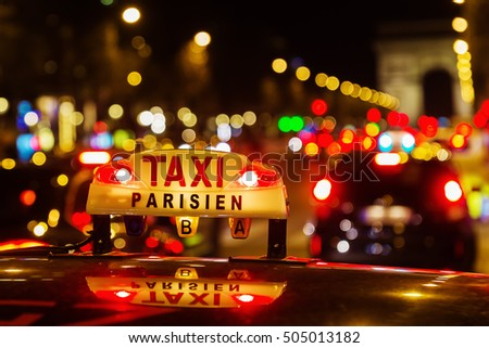 neon sign of a Parisian taxi on the Champs-Elysees at night