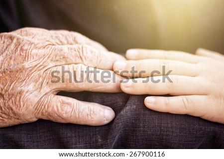 nephew touching grandfather's hand in sunlight - stock photo