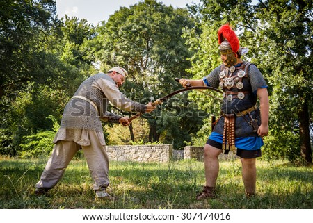 NEPTUN, ROMANIA - JULY 28, 2015 - Ancient Festival - Reenactment of the Roman and  Dacian (Thracian) wars - Roman centurion fighting a Dacian soldier with a sica (falx, sickle)