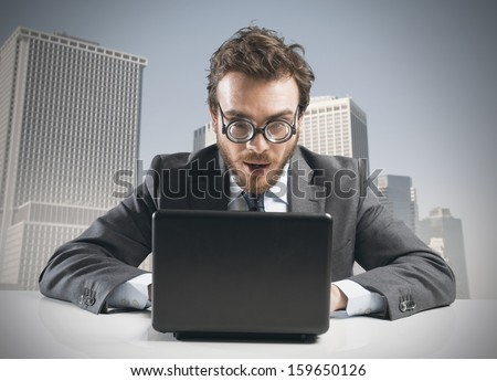 Nerd businessman working with a laptop on a desk - stock photo