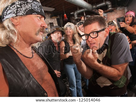 Nerd confronting tough gang member in leather vest in bar