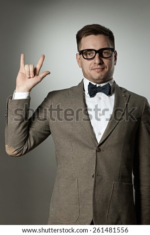 "Nerd in eyeglasses and bow tie showing ""rock on"" gesture against grey background - stock photo"