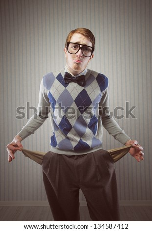 Nerd man stands holding his pockets out showing that he has no money - stock photo